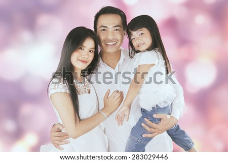 Portrait of two parents and their daughter smiling at the camera, shot with a bokeh background - stock photo