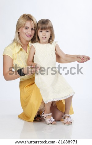 Portrait of two persons smiling, mother and 5 years old daughter, studio image