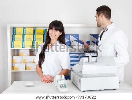 Portrait of two pharmacists at the drugstore smiling