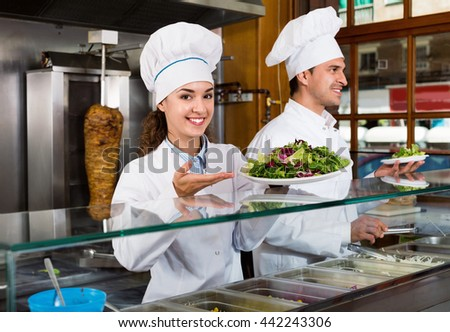 Portrait of two positive friendly hospitable chefs with kebab at fastfood place - stock photo