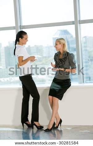 Portrait of two pretty colleagues having tea and chatting with each other - stock photo