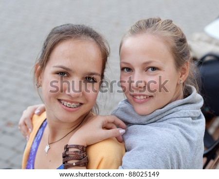 Portrait of two pretty student girls in the park - stock photo