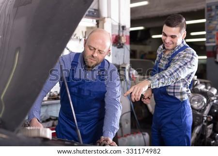 Portrait of two professional car mechanics at workshop - stock photo
