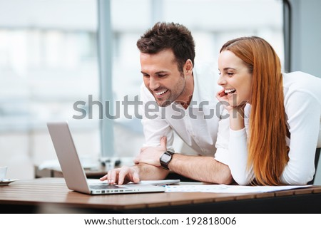 Portrait of two professionals looking at a laptop screen - stock photo