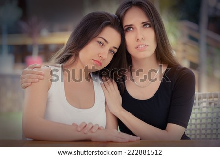 Portrait of two sad girls - Young woman consoling her best friend - stock photo