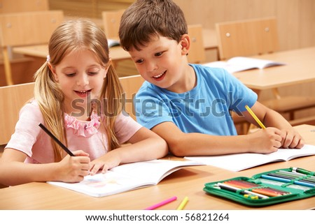 Portrait of two schoolchildren sitting by one desk during drawing lesson while boy looking at his mate?s copybook