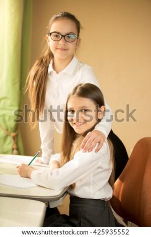 Portrait of two schoolgirls posing behind desk at bedroom - stock photo