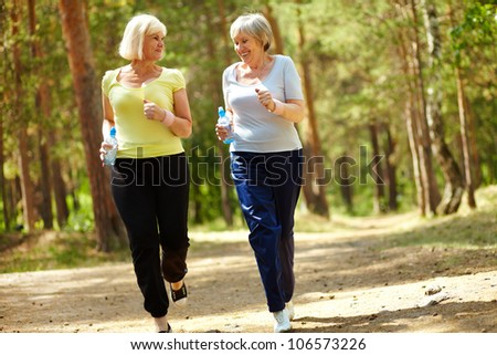 Portrait of two senior females running outdoors - stock photo