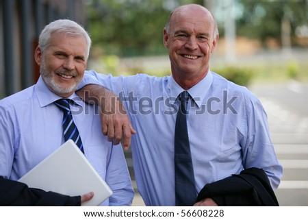 Portrait of two senior men smiling in suit - stock photo
