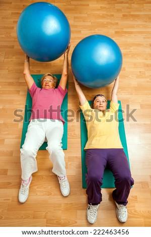 Portrait of Two senior women doing abdomen exercises with body ball in heath club. - stock photo