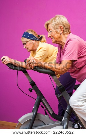 Portrait of two Senior women doing spinning exercise together in gym.