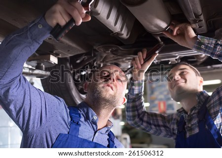 Portrait of two serious professional car mechanics working together at garage - stock photo
