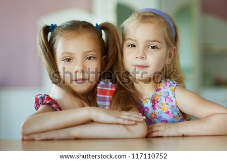 Portrait of two sisters close-up, which sits on table in room. - stock photo