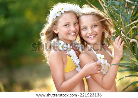 portrait of two sisters twins in tropical style - stock photo