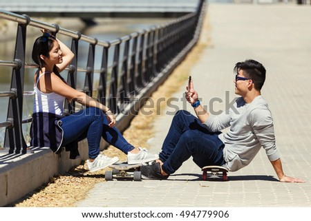 Portrait of two skaters using mobile phone in the street.