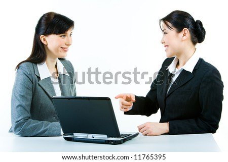 Portrait of two smiling business ladies sitting at laptop while one of the women pointing at its screen - stock photo