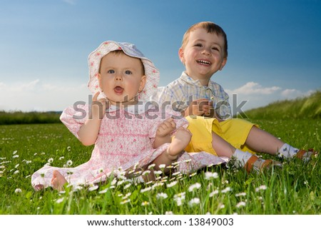 Portrait of two smiling children, a brother and sister, sitting in a green meadow. - stock photo
