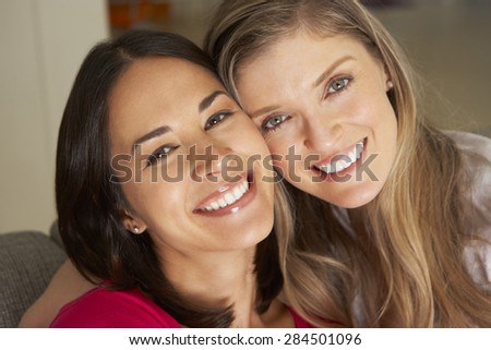 Portrait Of Two Smiling Female Friends On Sofa