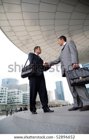 Portrait of two smiling men shaking hands - stock photo