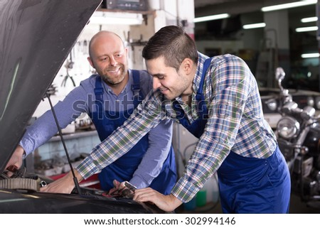 Portrait of two smiling professional car mechanics working together at workshop  - stock photo