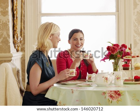 Portrait of two smiling young women having tea at dining table - stock photo