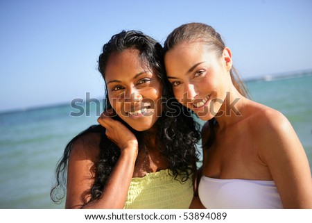 Portrait of two smiling young women in front of the sea - stock photo