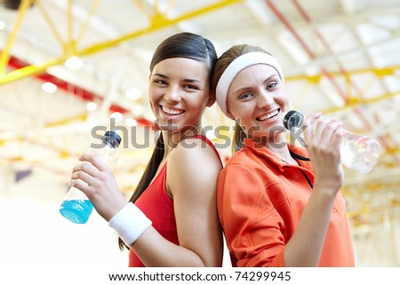 Portrait of two sporty girls with bottles of water looking at camera and smiling - stock photo