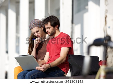 Portrait of two students sitting at campus looking at laptop together - stock photo