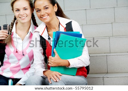 Portrait of two students sitting next to each other and looking at camera