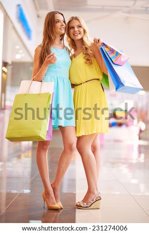 Portrait of two stylish girls with paperbags shopping in the mall - stock photo