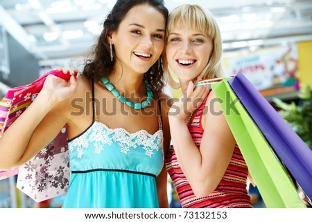 Portrait of two stylish women with paperbags looking at camera - stock photo