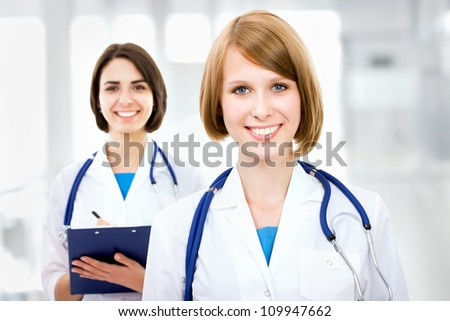 Portrait of two successful female doctors holding a writing pad - stock photo