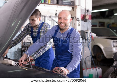 Portrait of two successful smiling car mechanics at workshop  - stock photo