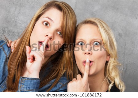 Portrait of two surprised young teenage women holding their fingers at the mouth, looking at the camera. Studio shot against a gray background. - stock photo