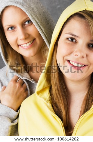 Portrait of two teen girls in hooded jackets cheerfully smiling into the camera. Studio shot against a gray background. - stock photo