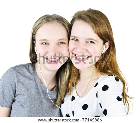 Portrait of two teenage girl friends listening to music sharing earphones - stock photo