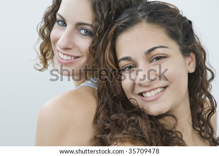 Portrait of two teenage girls smiling back to back - stock photo