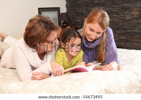 Portrait of two women and a little girl stretched out on a bed reading a book - stock photo