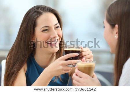 Portrait of two women friends talking holding coffee cups in a restaurant - stock photo