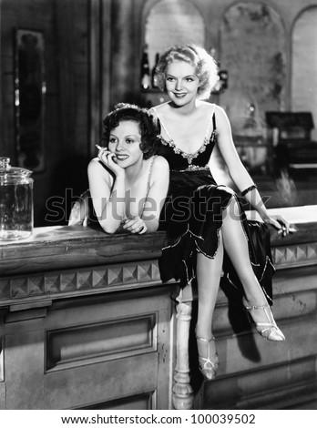 Portrait of two women smoking on bar - stock photo