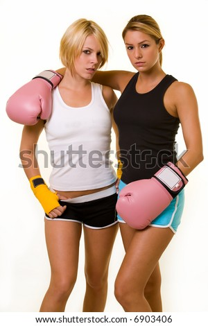 Portrait of two women wearing shorts and tank top one wearing pink boxing gloves and one wearing yellow hand wraps