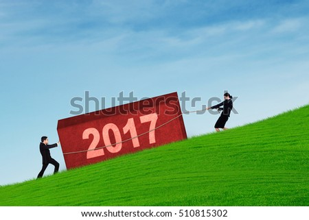 Portrait of two workers collaborate pulling a boulder with number 2017