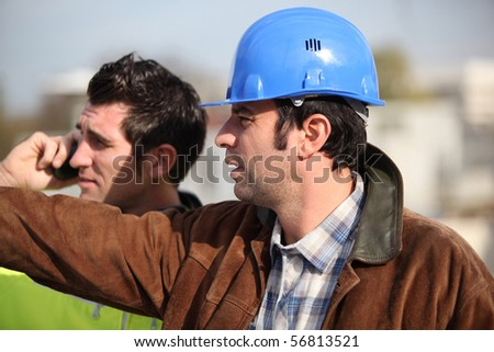 Portrait of two workers looking away - stock photo