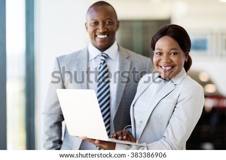 portrait of two workers with laptop inside car showroom - stock photo