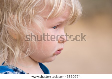 portrait of two years old sad blond girl