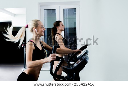 Portrait of Two young adult cute sporty women run on machine in the gym center Beautiful girls with white headphone inside on on wall and window background Couple of sport girls with fly hair - stock photo