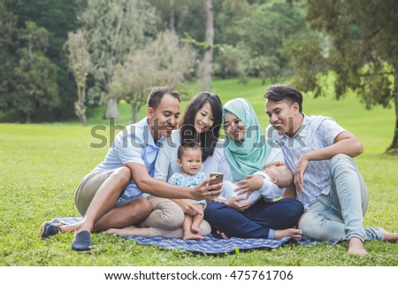 portrait of two young asian family in the park looking at mobile phone
