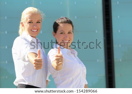 portrait of two young attractive business women with thumb up - stock photo