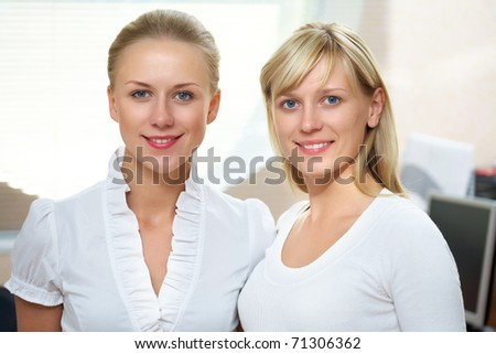 Portrait of two young beautiful business women in front of windows with shutters