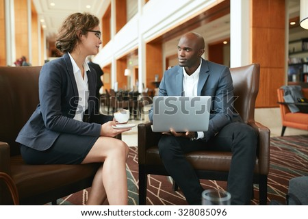 Portrait of two young business colleagues sitting at coffee shop. African businessman with laptop and businesswoman with cup of coffee discussing work. - stock photo